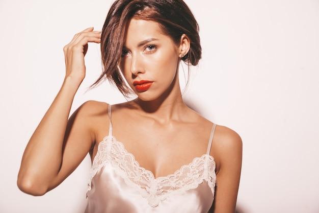 Retrato de uma linda mulher morena sensual. garota com roupas clássicas bege elegantes. modelo com lábios vermelhos isolado no branco