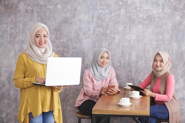 Retrato de uma linda mulher muçulmana sorrindo e em pé enquanto segura o laptop e seus irmãos nas costas