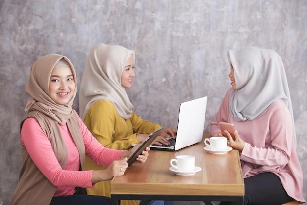 Retrato de uma linda mulher muçulmana sorrindo e segurando o tablet enquanto seus irmãos conversam ao fundo