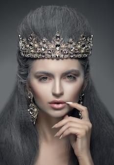 Retrato de uma linda mulher na coroa de diamante e brincos