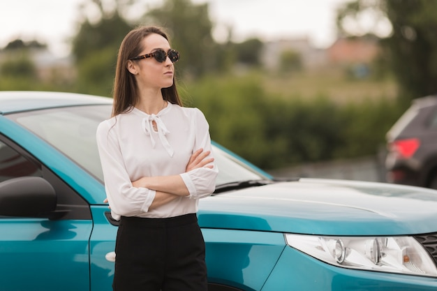 Retrato de uma linda mulher na frente de um carro