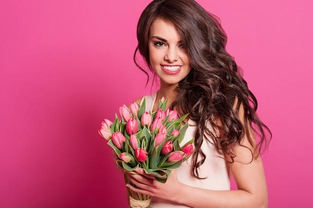 Retrato de uma linda mulher natural com tulipas cor de rosa