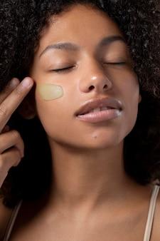 Retrato de uma linda mulher negra aplicando a base