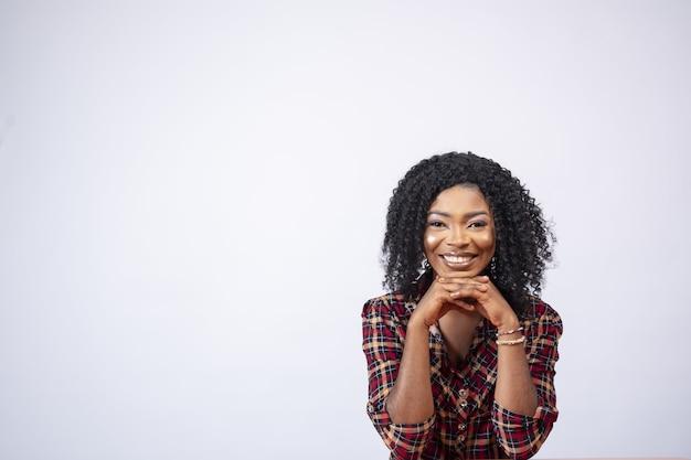 Retrato de uma linda mulher negra sentada em uma mesa em frente a um fundo branco