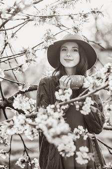 Retrato de uma linda mulher no jardim de macieira flor na primavera no pôr do sol. imagem em estilo de cor preto e branco