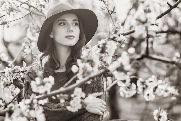 Retrato de uma linda mulher perto de jardim de macieira flor na primavera no pôr do sol. imagem em estilo de cor preto e branco