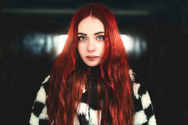 Retrato de uma linda mulher ruiva em pé na passagem subterrânea