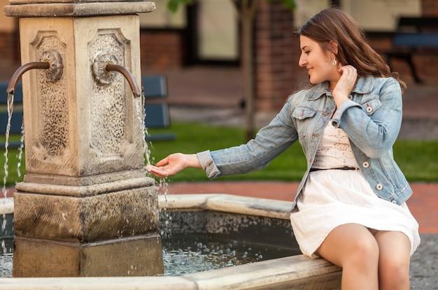 Retrato de uma linda mulher segurando a mão sob a fonte
