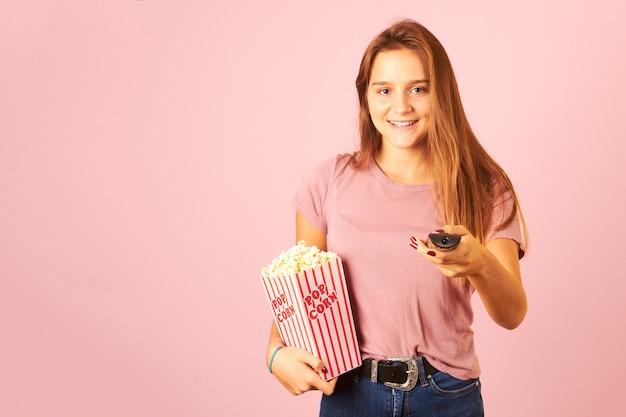 Retrato de uma linda mulher segurando o controle remoto e comendo pipoca