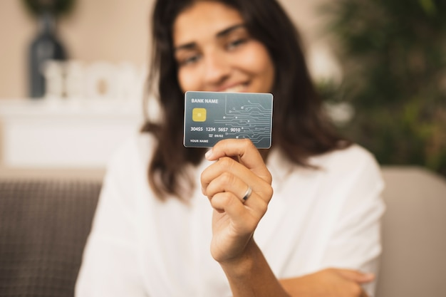 Retrato de uma linda mulher segurando um cartão de crédito