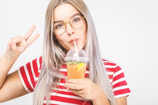 Retrato de uma linda mulher segurando um copo de suco de laranja. retrato isolado de menina sorridente sobre branco. roupas casuais.