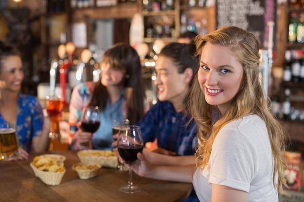 Retrato de uma linda mulher segurando uma bebida enquanto está sentado com amigos