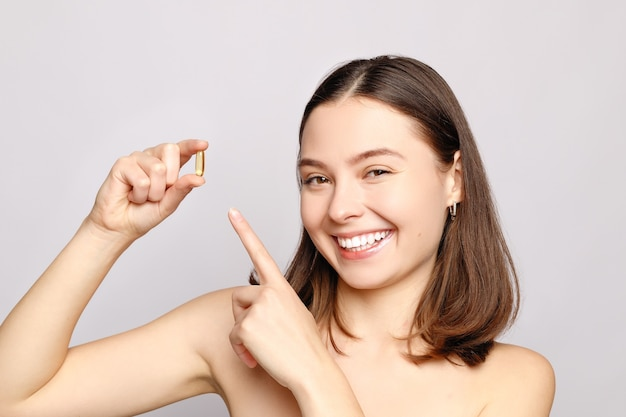 Retrato de uma linda mulher segurando uma pílula de óleo de fígado de bacalhau