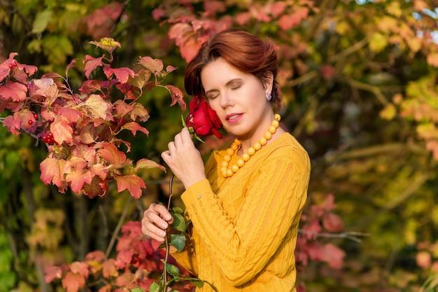 Retrato de uma linda mulher segurando uma rosa e em pé perto da folhagem vermelha em um arbusto viburno com os olhos fechados no parque outono