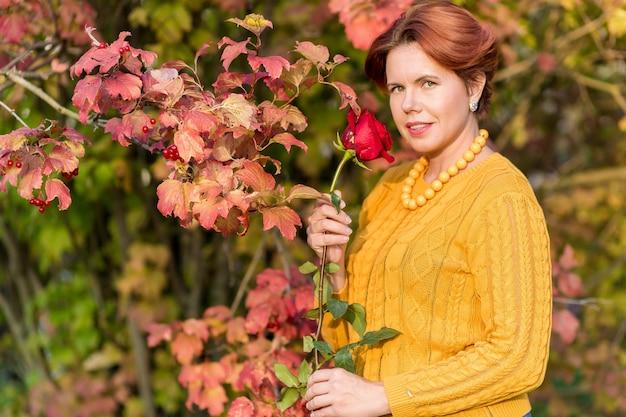 .retrato de uma linda mulher segurando uma rosa e em pé perto da folhagem vermelha em um arbusto viburno no parque outono