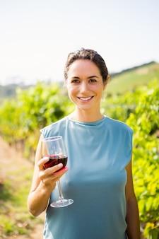 Retrato de uma linda mulher segurando vinho tinto