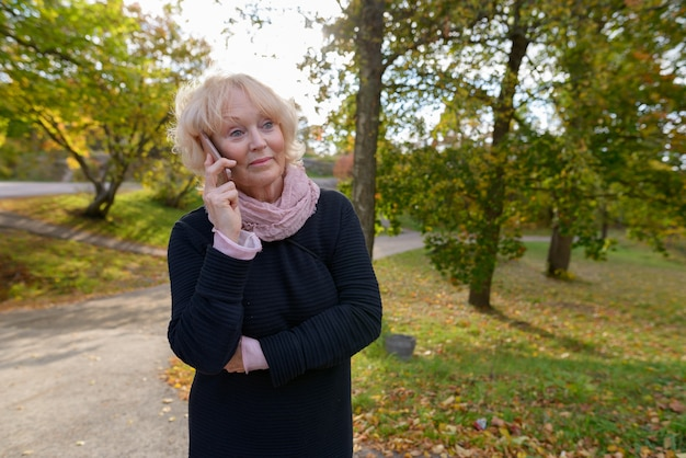 Retrato de uma linda mulher sênior com cabelo loiro curto relaxante no parque ao ar livre no outono