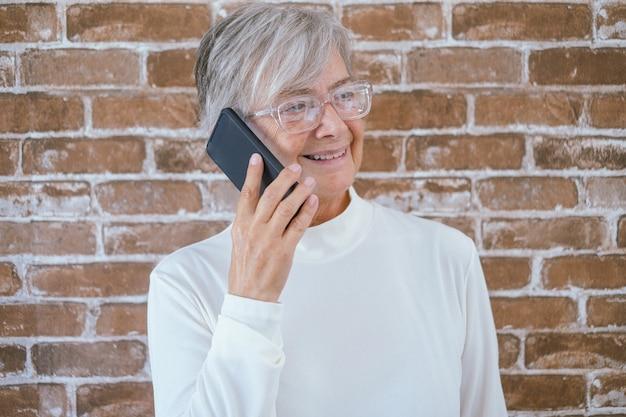Retrato de uma linda mulher sênior de cabelos brancos, usando o telefone, em pé contra uma parede de tijolos, sorrindo
