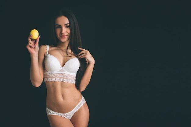 Retrato de uma linda mulher sensível em roupa interior segurando limão perto do rosto.