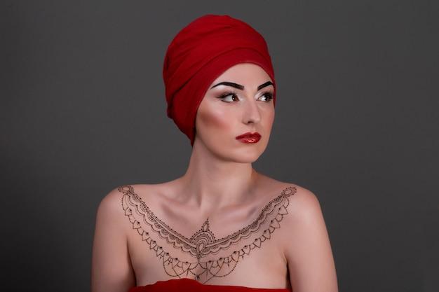 Retrato de uma linda mulher sensual com maquiagem de noite e tatuagem de henna sobre brest, cachecol isolado de parede cinza, vermelho