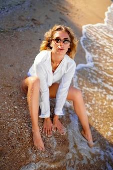 Retrato de uma linda mulher sexy caucasiana tomando banho de sol com óculos de sol