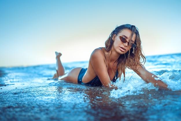 Retrato de uma linda mulher sexy caucasiana tomando banho de sol em óculos de sol com estampa de leopardo e cabelo comprido em ...