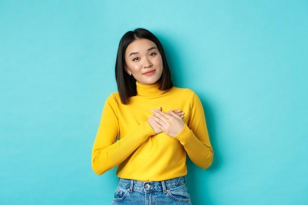 Retrato de uma linda mulher sincera, segurando o coração de mãos dadas, sorrindo e ouvindo compassivo, em pé sobre um fundo azul em uma camisola amarela