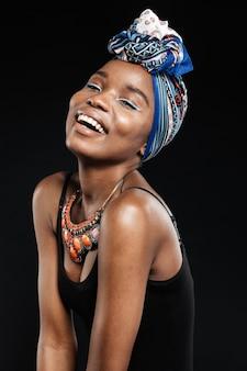 Retrato de uma linda mulher sorridente, posando com os olhos fechados, em estúdio, isolado na parede preta