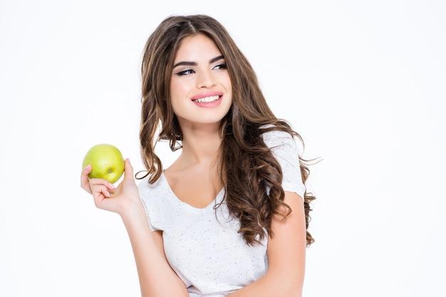 Retrato de uma linda mulher sorridente segurando uma maçã e olhando para longe, isolado em uma parede branca