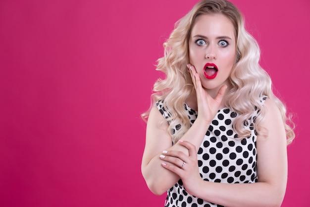 Retrato de uma linda mulher surpresa. uma garota charmosa com maquiagem perfeita se emociona e abre a boca de surpresa. tiro na cabeça. emoções. isolado em uma parede rosa