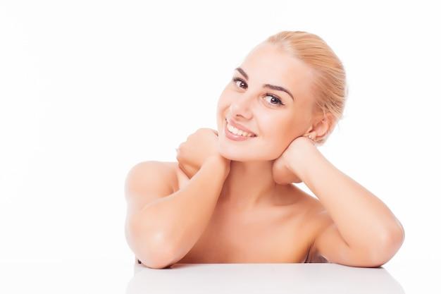 Retrato de uma linda mulher tocando a pele do rosto e sorrindo