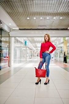 Retrato de uma linda mulher vestindo blusa vermelha, jeans casual e sapatos de salto altos pretos posa com bolsa de couro vermelho em enorme shopping center.