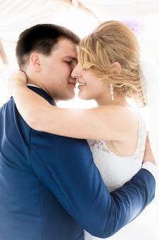 Retrato de uma linda noiva e do noivo se beijando na primeira dança