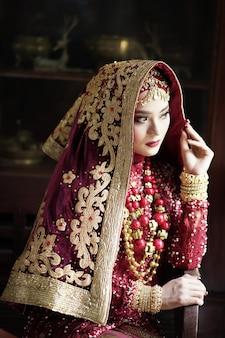 Retrato de uma linda noiva indiana em um vestido dourado e vermelho