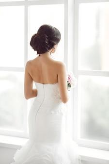Retrato de uma linda noiva olhando para a janela, foto por trás