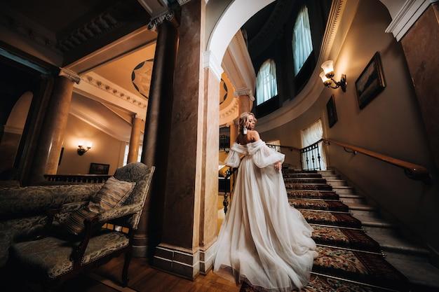 Retrato de uma linda noiva subindo uma bela escadaria.