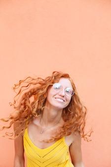 Retrato de uma linda ruiva alegre com cabelos cacheados voando e sorrindo