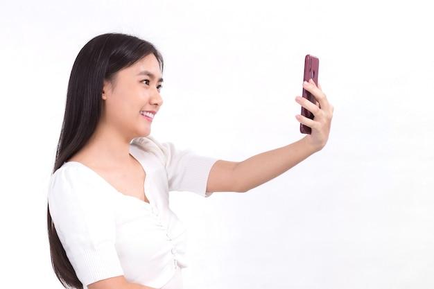 Retrato de uma linda senhora asiática com cabelo comprido preto e camisa branca segurando o smartphone