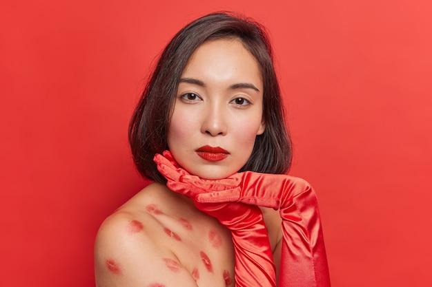Retrato de uma linda senhora asiática com cabelo escuro com as mãos embaixo do queixo fica lateralmente contra a parede vermelha olha diretamente para a câmera tem traços de beijos em poses de corpo nu dentro de casa usa luvas compridas