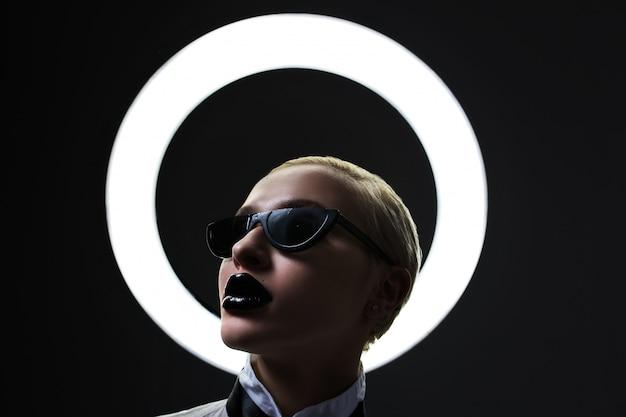 Retrato de uma loira elegante usando óculos escuros e lábios pretos rezando. lâmpada redonda