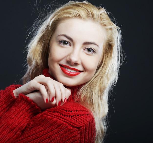Retrato de uma loira encantadora e sorridente com um suéter vermelho