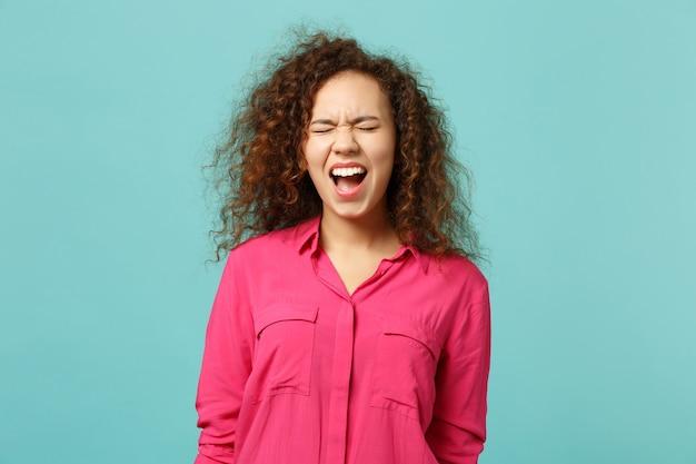 Retrato de uma louca garota africana gritando em roupas rosa casuais, mantendo os olhos fechados, isolados no fundo da parede azul turquesa no estúdio. conceito de estilo de vida de emoções sinceras de pessoas. simule o espaço da cópia.