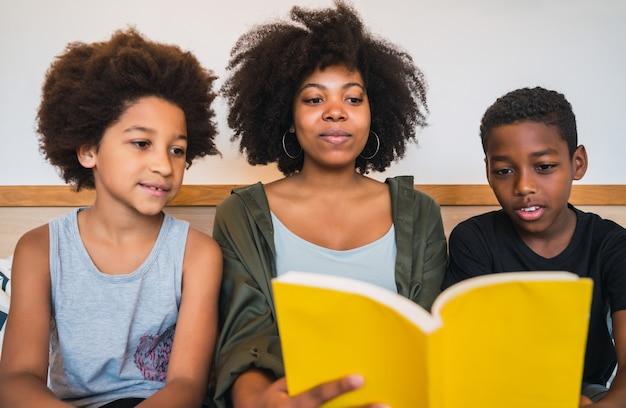 Retrato de uma mãe afro-americana lendo um livro para os filhos em casa. conceito de família e estilo de vida.
