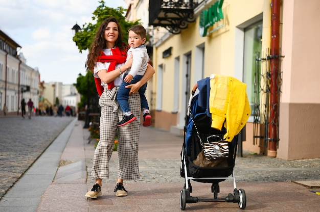 Retrato de uma mãe alegre e bebê na cidade