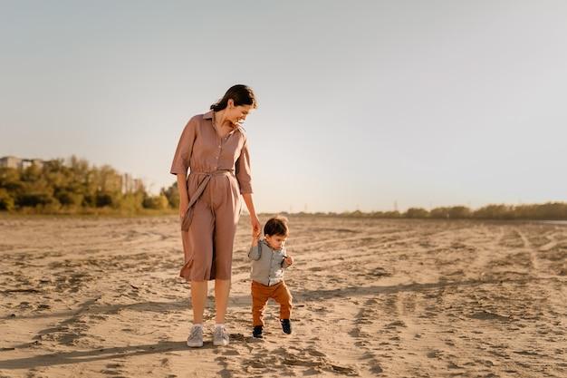 Retrato de uma mãe amorosa e seu filho de um ano andando e brincando com areia.
