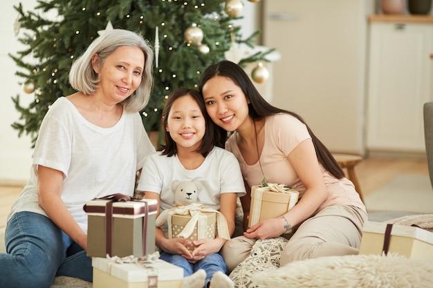 Retrato de uma mãe asiática feliz com suas duas filhas sorrindo, sentadas no chão, comemorando o natal juntas