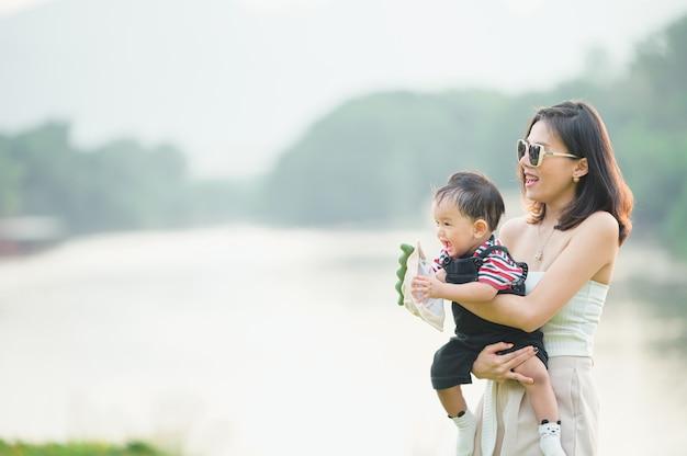 Retrato de uma mãe asiática sorrindo com seu filho de 11 meses ao ar livre