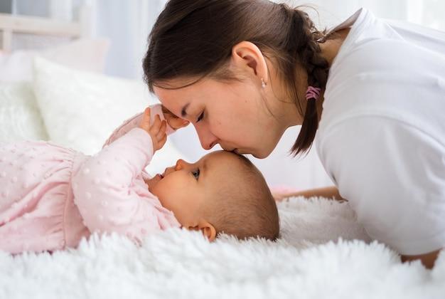 Retrato de uma mãe beijando sua filha bebê na cama Foto Premium