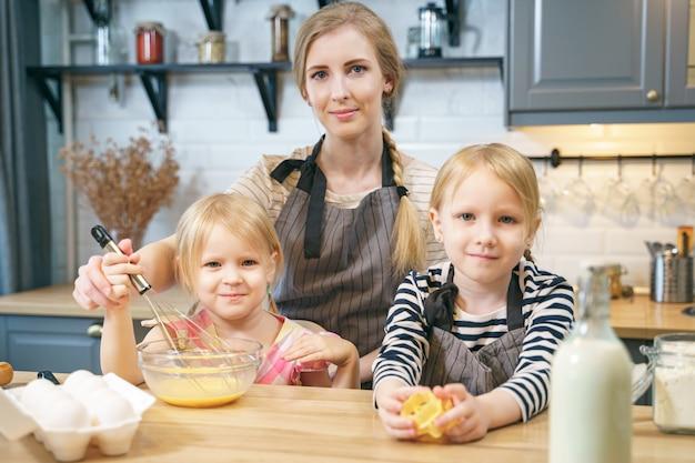 Retrato de uma mãe de família feliz e duas filhas bonitos preparando biscoitos caseiros na cozinha