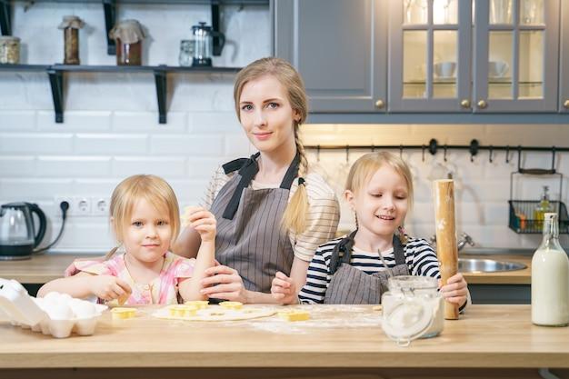 Retrato de uma mãe de família feliz e duas filhas bonitos preparando biscoitos caseiros na cozinha.